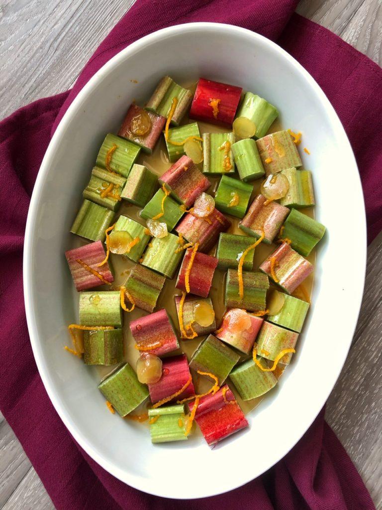 Auflaufform mit rohen Rhabarberstücken, belegt mit Orangenschale und Ingwer in Scheiben