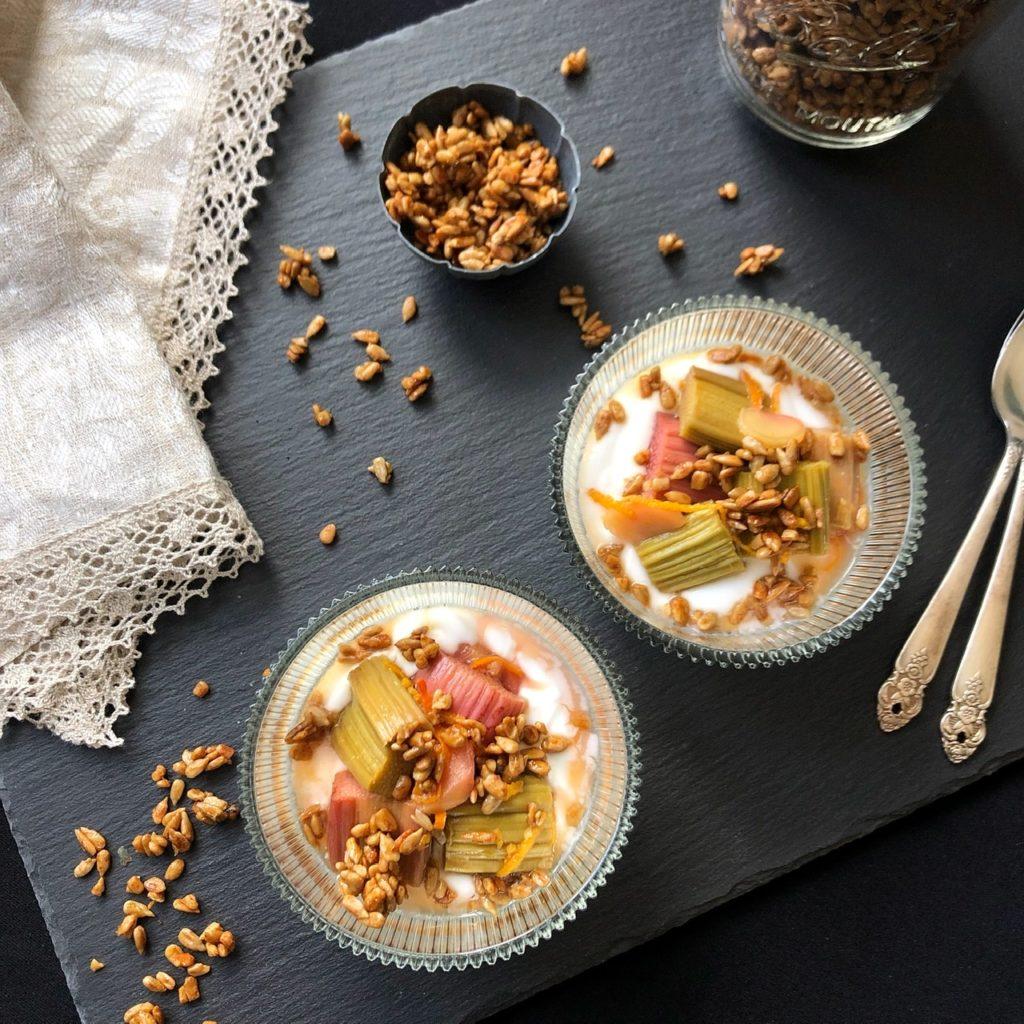 Geröstete Sonnenblumenkerne mit Honig und Salz auf zwei Gläsern mit Joghurt und Ofen-Rhabarber