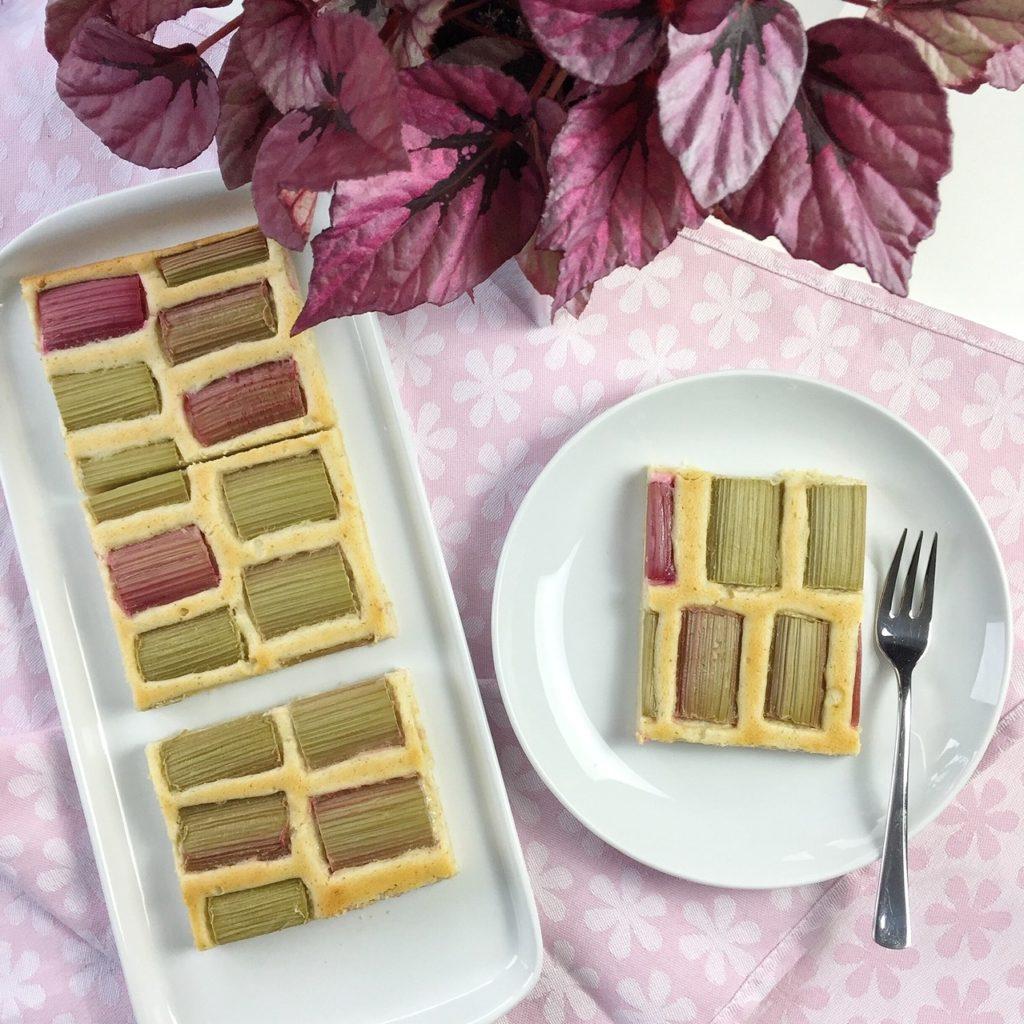 Rhabarberkuchen mit Vanille-Quark-Creme auf einer Kuchenplatte. Ein Kuchenteller mit einem Stück Rhabarberkuchen und einer Gabel.