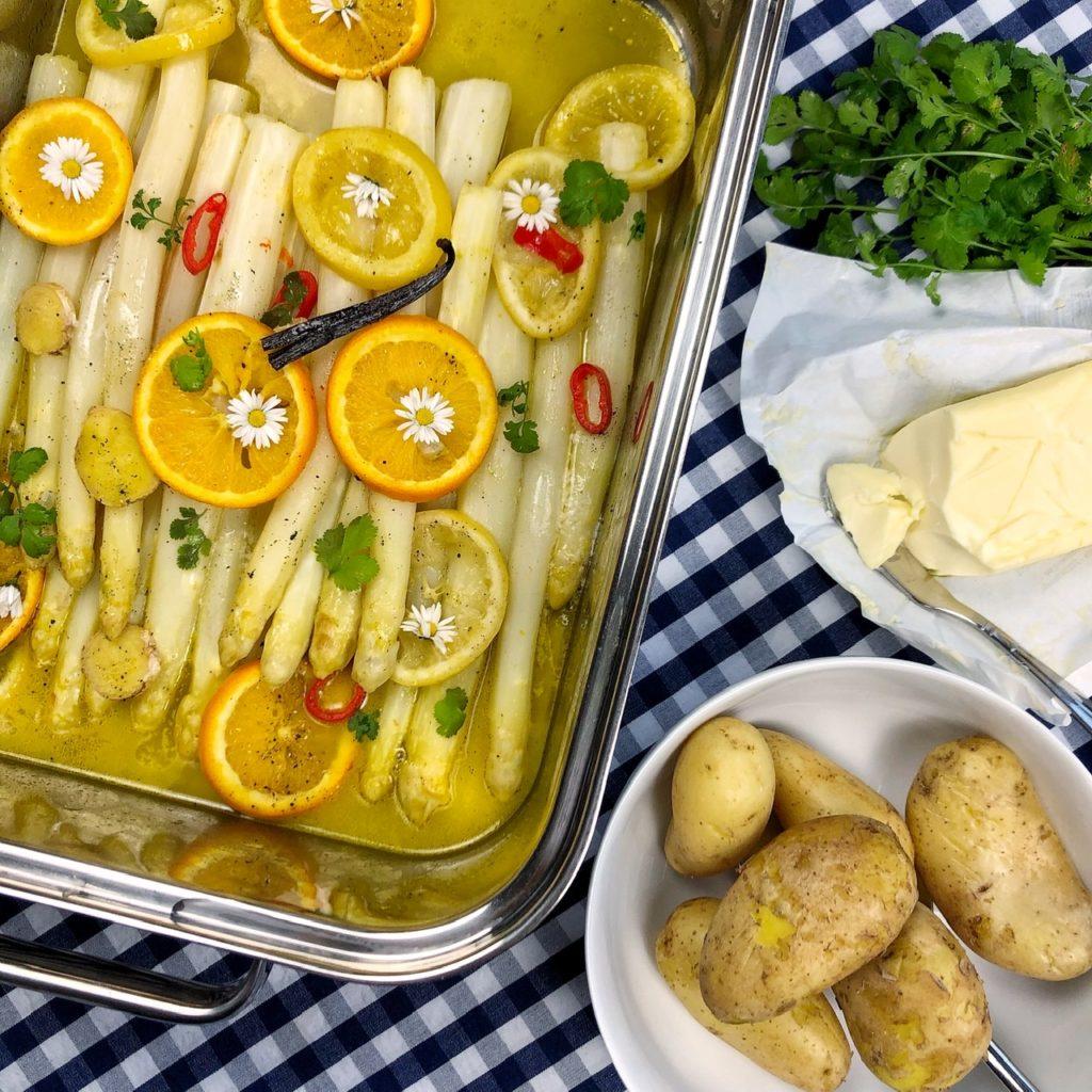 Ein Bräter mit weißem Spargel, Orangen- und Zitronenscheiben, Chili, Ingwer, Vanille, Gänseblümchen. Eine Schüssel mit Kartoffeln. Butter im Papier. Ein Bund Koriander.