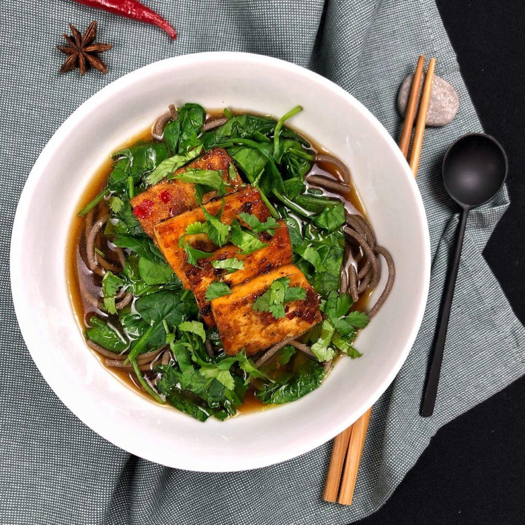 Eine weiße Schüssel mit dunkler Brühe, Soba-Nudeln, Spinat und Tofu-Scheiben. Essstäbchen, ein schwarzer Löffel. Sternanis. Chilischote.