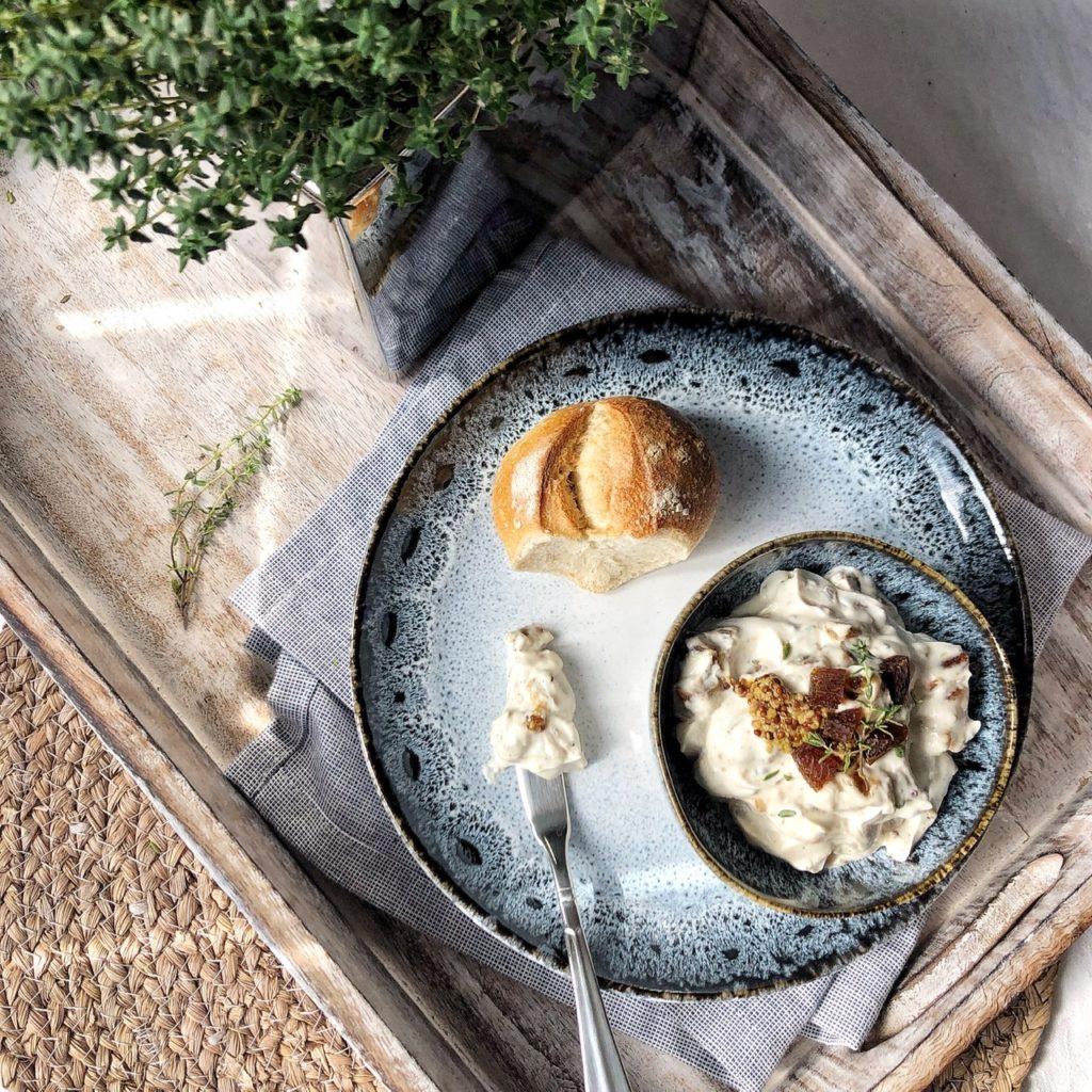 Ein Tablett mit einem Teller und einer Schale mit Ziegenfrischkäsecreme mit Aprikosen und Thymian, ein Brötchen, ein Messer mit Creme.