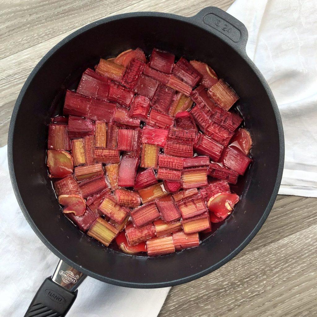 Eine schwarze Pfanne mit roten gegarten Rhabarberstücken und Ingwerscheiben in Roséwein.