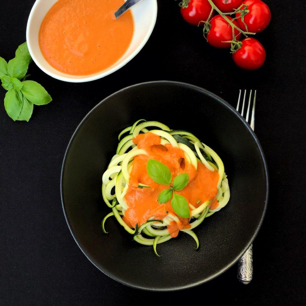 Auf schwarzem Hintergrund steht eine schwarze Schale mit Zucchini-Spiralen (Zoodles) mit Paprika-Sauce und Basilikum-Garnitur. Darum sind Basilikum, ein Schälchen Paprika-Sauce und Tomaten Dekoriert. Rechts neben der Schale liegt eine Gabel.
