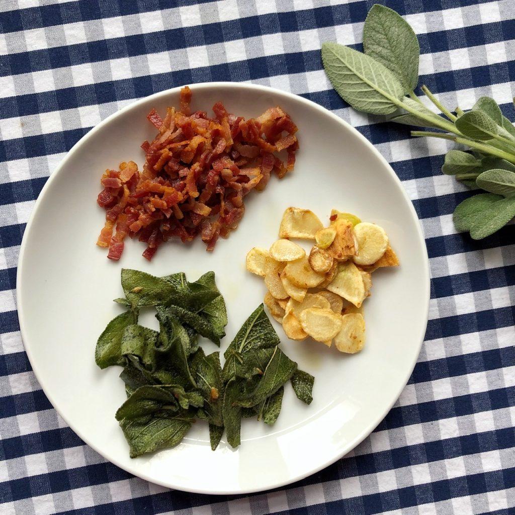 Ein Teller mit ausgebratenen Speckwürfeln, goldbraunen Knoblauchscheiben und frittierten Salbeiblättern.