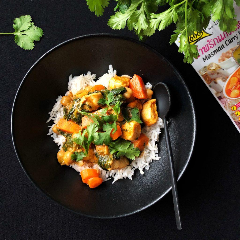 Eine schwarze Schüssel auf schwarzem Untergrund. Darin weißer Reis mit Massaman-Curry: Hähnchenstücke, Spinat, Möhren und Kichererbsen in Currysauce. Mit frischem Koriander bestreut, der auch oben rechts ins Bild ragt. Ein Beutel mit Massaman-Currypaste ragt rechts ins Bild.