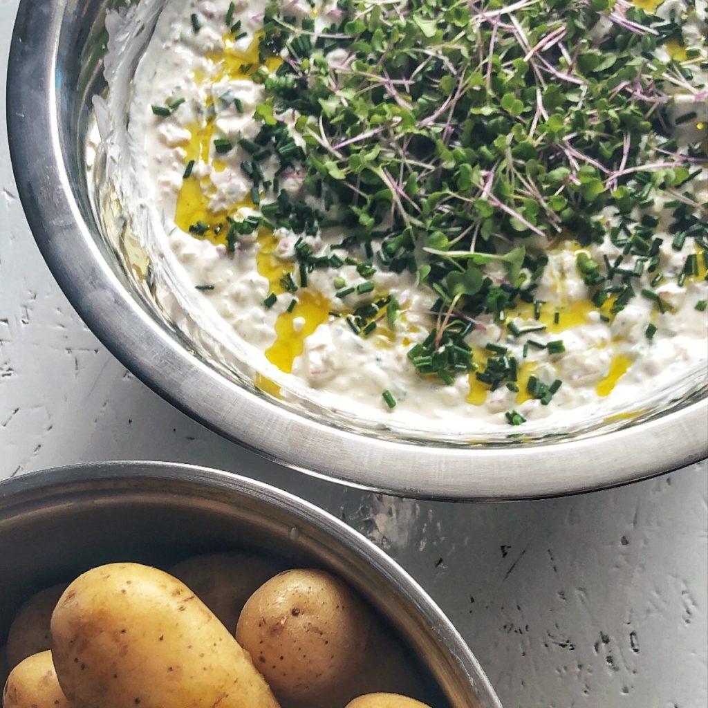 Oben rechts eine Schüssel mit Radieschen-Kräuterquark mit ganz viel frischen Kräutern on top und mit Olivenöl beträufelt. Links unten ein Topf mit gekochten Kartoffeln mit Schale.