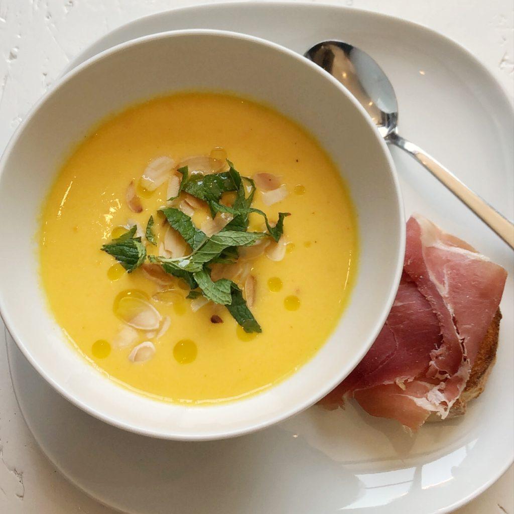 Ein weißer Teller, darauf eine weiße Suppenschüssel mit orange-gelber Gazpacho, die mit Mandelblättchen, Minze und Olivenöl dekoriert ist. Daneben ein Crostini mit Serrano-Schinken.