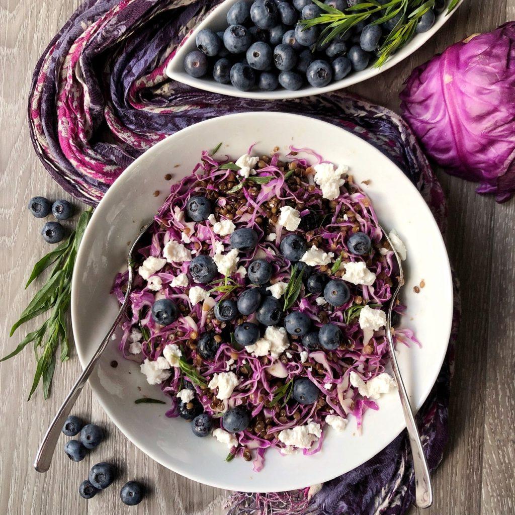 In der Mitte steht eine weiße Schüssel mit Linsensalat mit violettem Spitzkohl, Blaubeeren, Feta und Estragonblättchen. Darum dekoriert liegt ein pink-violetter Schal, einzelne Blaubeeren und Blaubeeren in einer schmalen weißen Schale, Estragonzweige und ein halber violetter Spitzkohl.