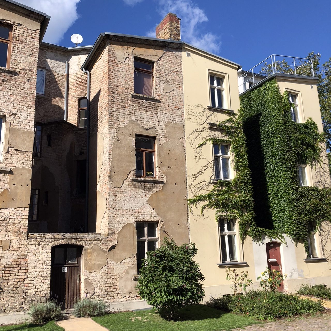 Ein Doppelhaus in Brandenburg, rechte Seite top saniert, links völlig unrenoviert, mit abbröckelndem Putz.