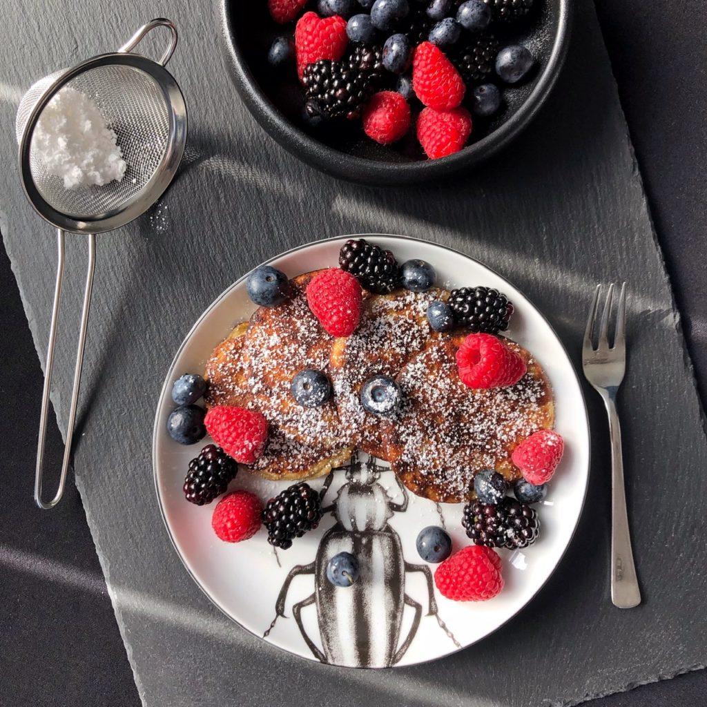 Auf einer von der Sonne beschienen Schieferplatte steht ein Teller mit kleinen Pancakes, bestreut mit Puderzucker und frischen gemischten Beeren. Eine kleine Schüssel mit Beeren ragt oben ins Bild, links ein Sieb mit Puderzucker.