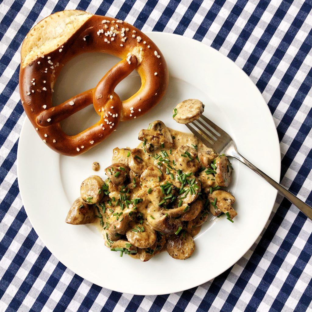 Auf einer blau-weiß karierten Tischdecke steht ein weißer Teller mit Weißwurstpfanne mit Senfsauce und einer Laugenbrezel als Beilage.