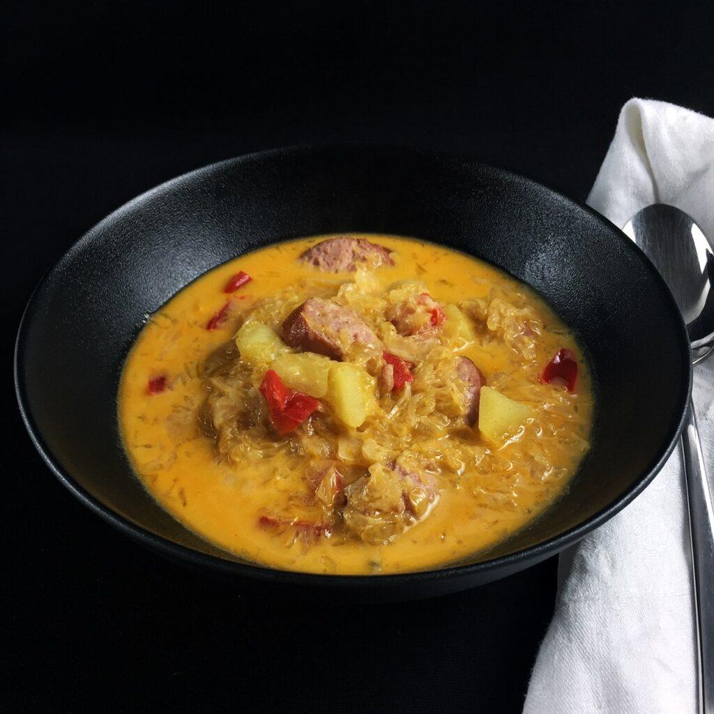 Eine schwarze Suppenschalen auf schwarzem Hintergrund. Darin goldgelbe Sauerkrautsuppe mit Kartoffel- und roten Paprikastückchen und Mettwurst in Scheiben. Rechts daneben liegt eine weiße Serviette und ein Löffel.