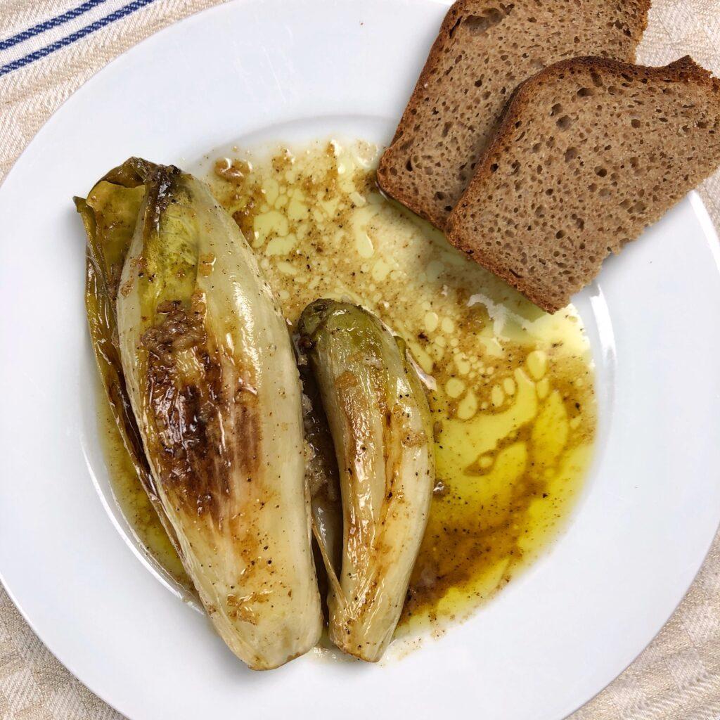 Ein weißer Teller, darauf liegt geschmorter Chicorée in einer Vinaigrette. Am Rand liegen zwei halbe Scheiben Vollkornbrot.