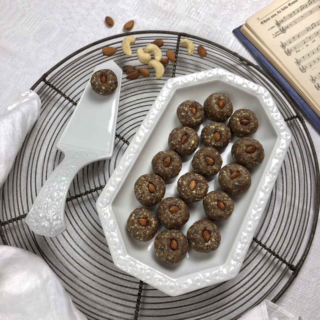 Man sieht einen antiken runden Kuchenrost auf einer weißen Tischdecke. Links unten in der Ecke liegt eine weiße Serviette, rechts oben ragt ein antiquarisches Gesangbuch ins Bild. Auf dem Rost steht eine weiße altmodische Porzellanschale (Maria Weß von Rosenthal) mit Zitronen-Mohn-Konfekt-Kugeln. Links daneben liegt ein weißer Tortenheber aus derselben Porzellan-Serie mit einer einzelnen Konfekt-Kugel darauf. Weiter oben auf dem Rost liegen ein paar Mandeln und Cashewkerne verstreut.