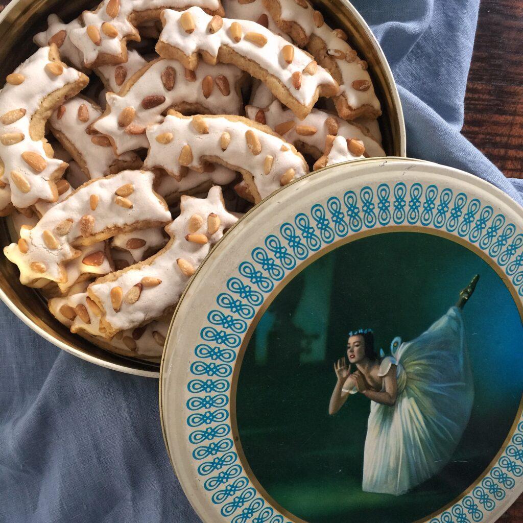 Auf einem hellblauen Tuch steht eine halbgeöffnete Keksdose mit einem altmodischen Ballerina-Motiv auf dem Deckel. In der Dose liegen sternschnuppenförmige Plätzchen mit einer Baiserschicht und darauf Pinienkernen.
