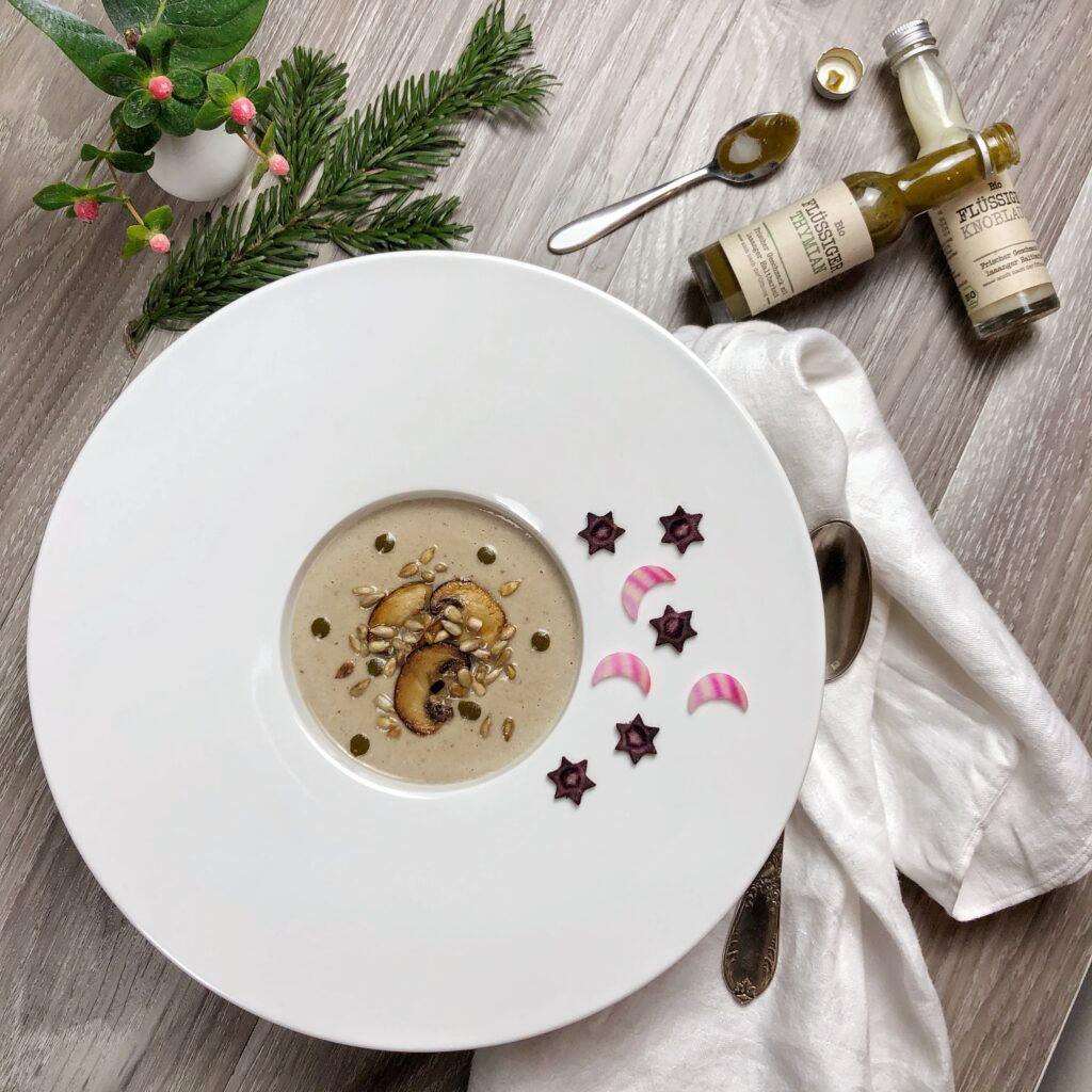 Auf einem grau-weiß gebeizten Holztisch steht ein weißer Suppenteller mit breitem Rand. Rechts daneben liegt eine etwas zerknüllte Serviette und ein Löffel. Oben rechts liegen zwei Fläschchen mit flüssigem Knoblauch und Thymian, daneben ein kleiner Löffel mit flüssigem Thymian darauf und der Verschluss dieser Flasche. Oben links liegt ein kleiner Tannenzweig, daneben steht eine kleine weiße Vase mit einem Zweig mit rosa Beeren. Im Teller befindet sich Champignon-Cremesuppe, garniert mit gebratenen Champignonscheiben, gerösteten Sonnenblumenkernen und Tropfen von flüssigem Thymian. Auf dem Tellerrand liegen Scheibchen von violetten Möhren, in Sternform ausgestochen, und Scheibchen von Ringelbete, in Mondform ausgestochen, zur Dekoration.