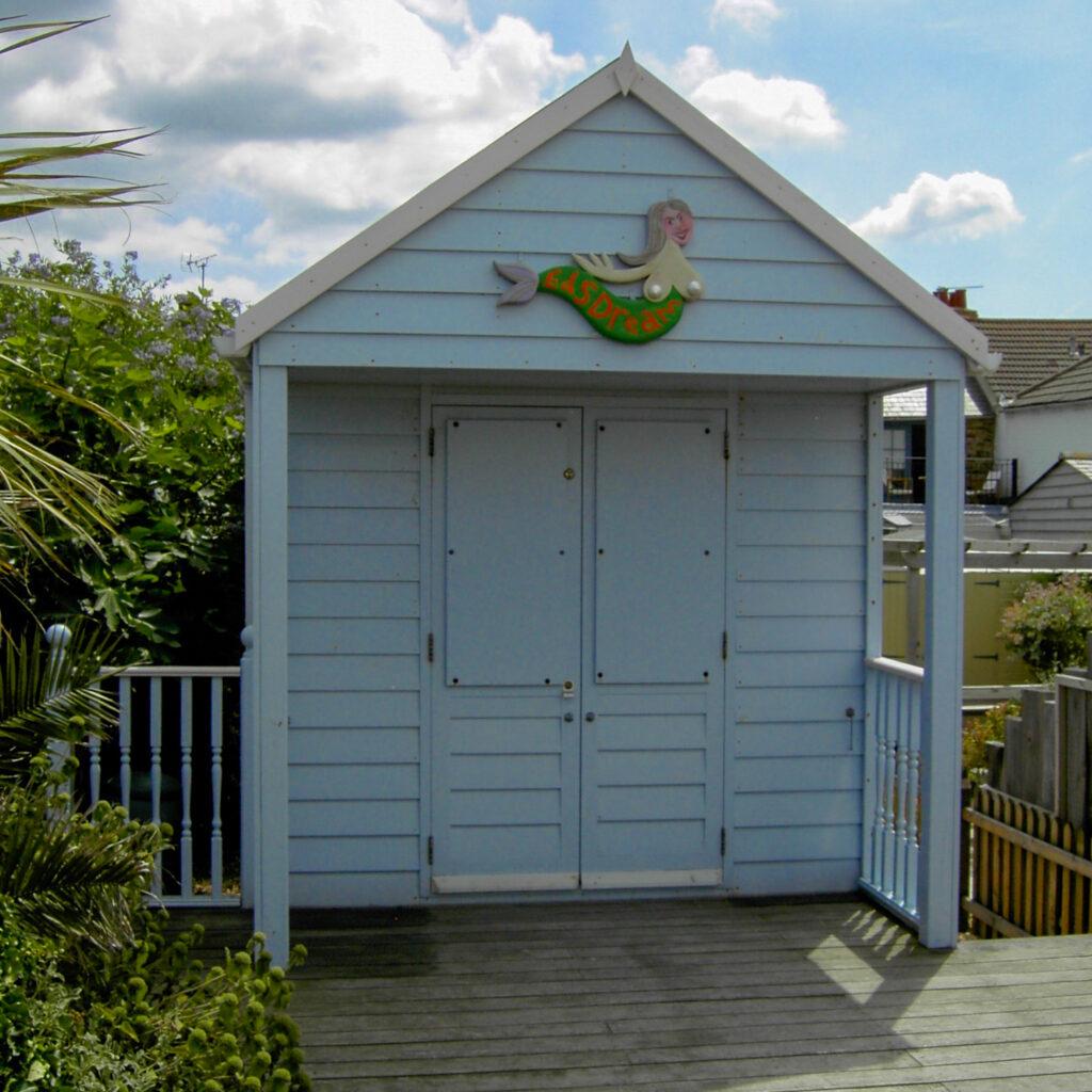 """Eine himmelblau gestrichene Strandhütte mit Holzveranda. Über der Tür hängt eine aus Holz geschnittene Meerjungfrau mit großen Brüsten, auf dem Schwanz steht """"Eds Dream""""."""