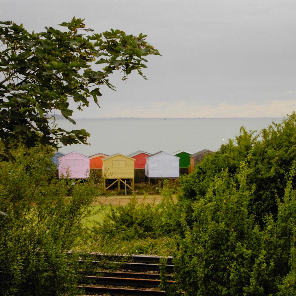Bunte Strandhütten am Strand von Whitstable, von hinten betrachtet mit Blick auf's Meer.