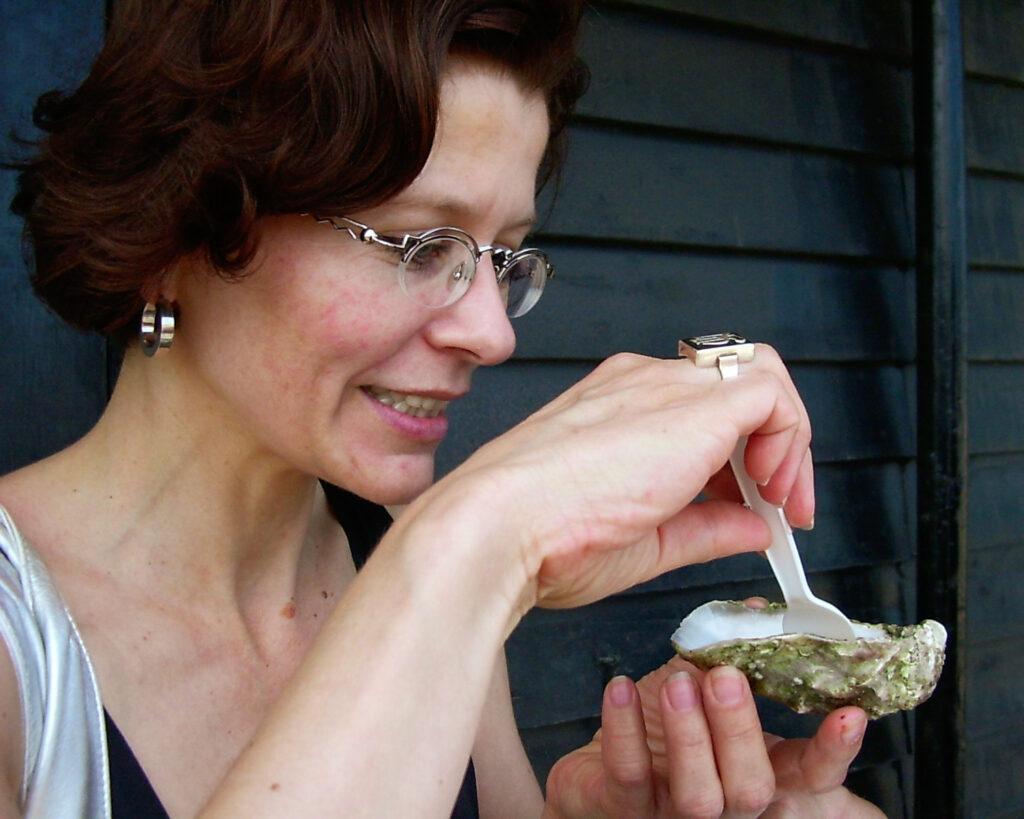 Odette steht vor dunklem Hintergrund und isst mit einer weißen Plastikgabel die erste Auster Ihres Lebens.