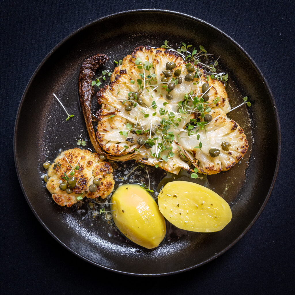 Ein schwarzer Teller auf schwarzem Untergrund. Darauf liegt ein ofengeröstetes Blumenkohlsteak - eine Scheibe mittig aus einem Blumenkohl geschnitten - mit Zitronen-Kapernbutter und Salzkartoffeln. Bestreut mit Rucola-Kresse.