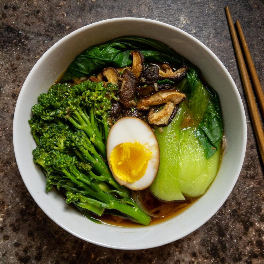 Auf braun geflecktem Untergrund steht eine weiße Suppenschalen gefüllt mit Miso-Suppe mit Soba-Nudeln, Bimi (oder Broccolini), Shiitake Pilzen, Pak Choi und einem halbierten Soja-Ei. Rechts daneben liegt ein karamellfarbenes Paar Essstäbchen.