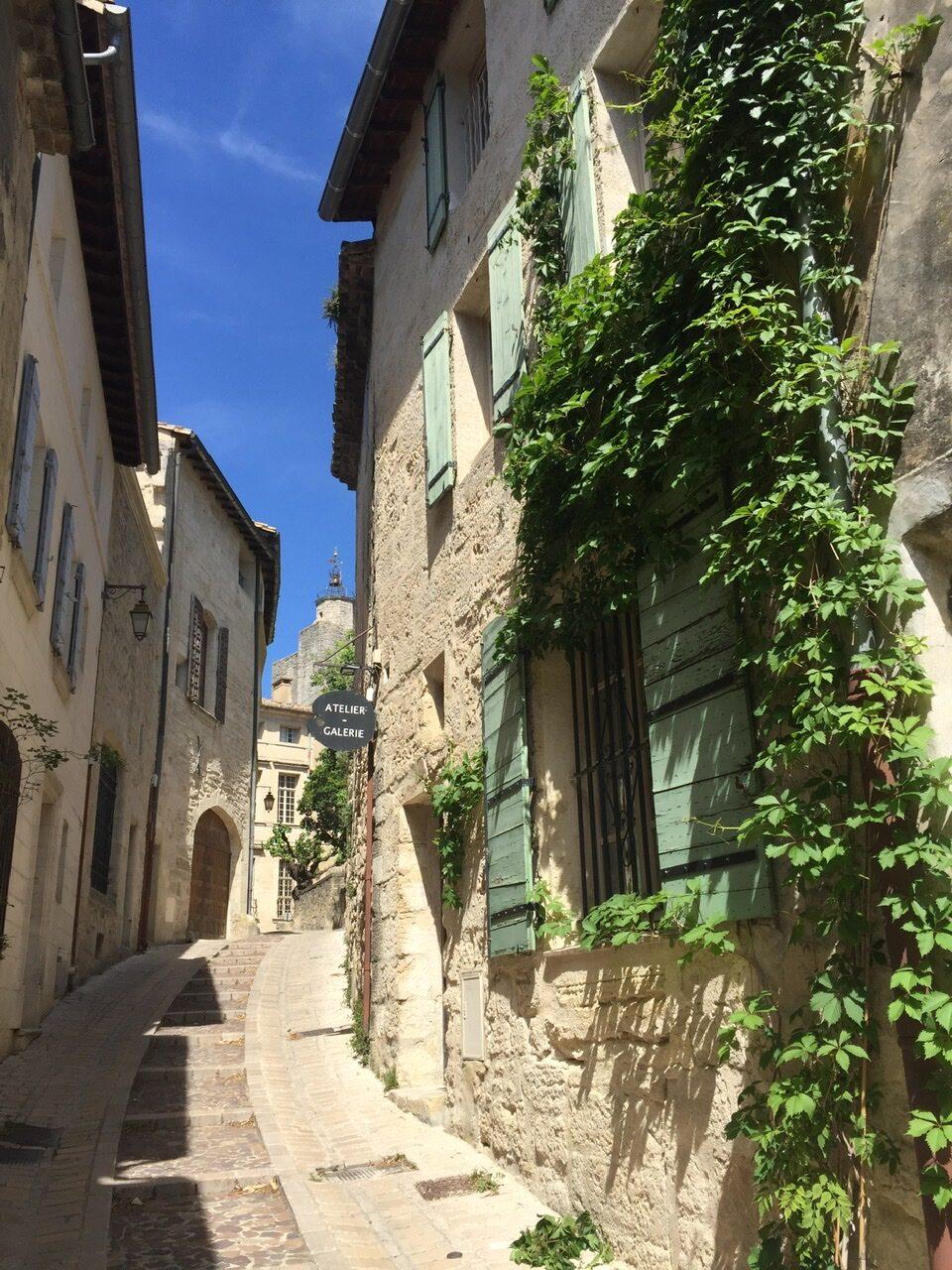 Eine ansteigende Gasse in der provençalischen Altstadt von Uzès. Rechts und links helle Sandsteinhäuser mit pastellfarbenen Fensterläden, zum Teil mit rankendem Wein bewachsen. Knallblauer Himmel und Sonne.