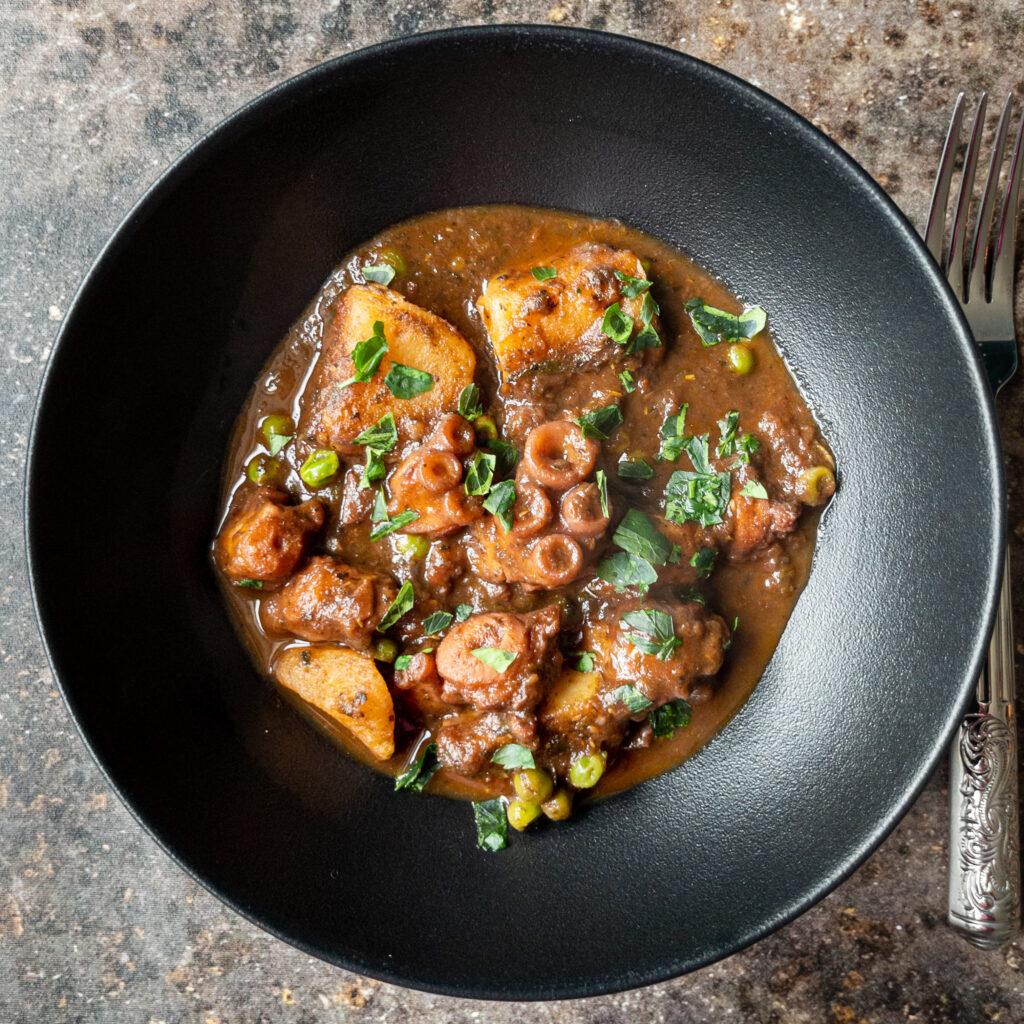Ein tiefer schwarzer Teller gefüllt mit Oktopus-Stew. Oktopusstücke, Kartoffelstücke und grüne Erbsen in einer sämigen braunen Soße. Sieht köstlich aus! Bestreut mit Petersilie.