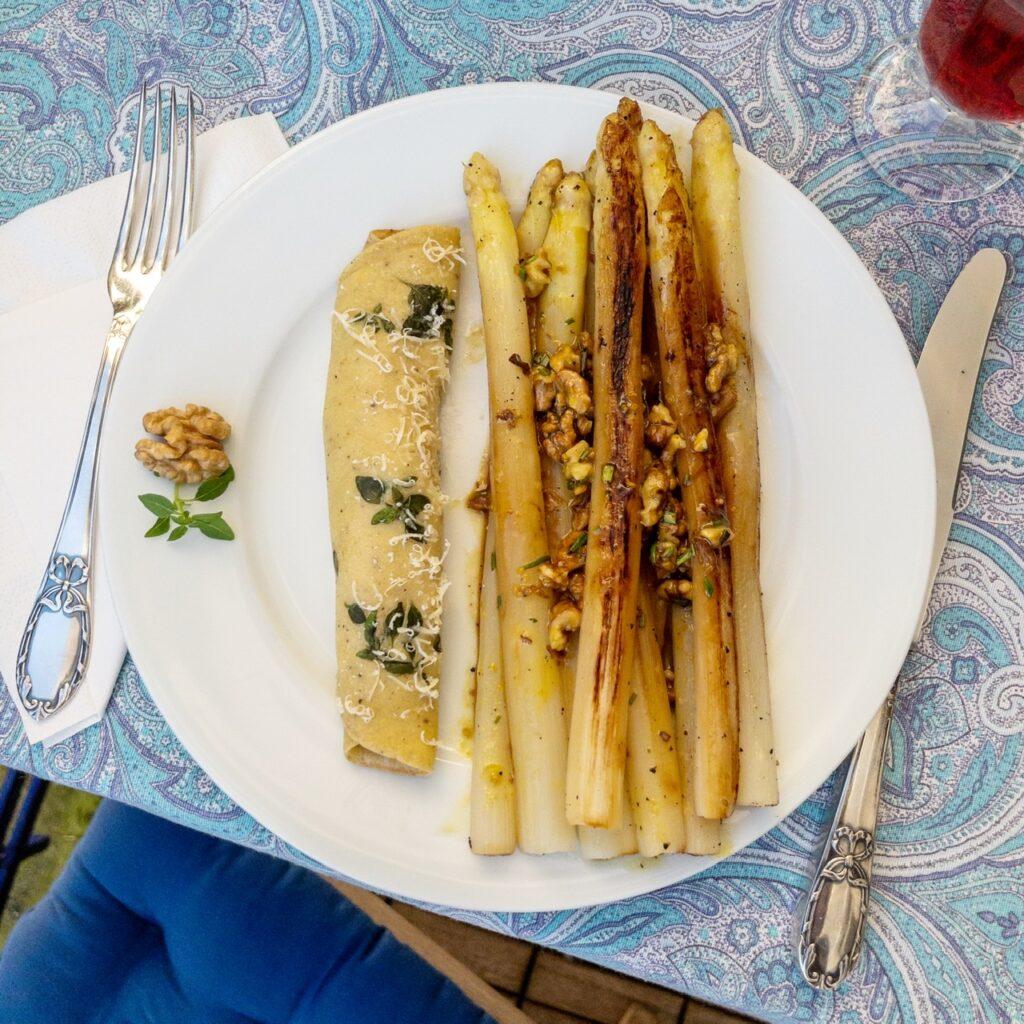 Blick von oben auf einen gedeckten Tisch. Tischdecke mit türkisblauem Paisleymuster, ein weißer Teller mit gebratenem weißem Spargel mit Honig-Walnuss-Vinaigrette und Basilikum-Pfannkuchen. Daneben Silberbesteck, eine weiße Papierserviette und ein Glas Rosé mit kräftiger Farbe. Ein Holzstuhl mit blauem Sitzkissen ragt vorne links ins Bild.