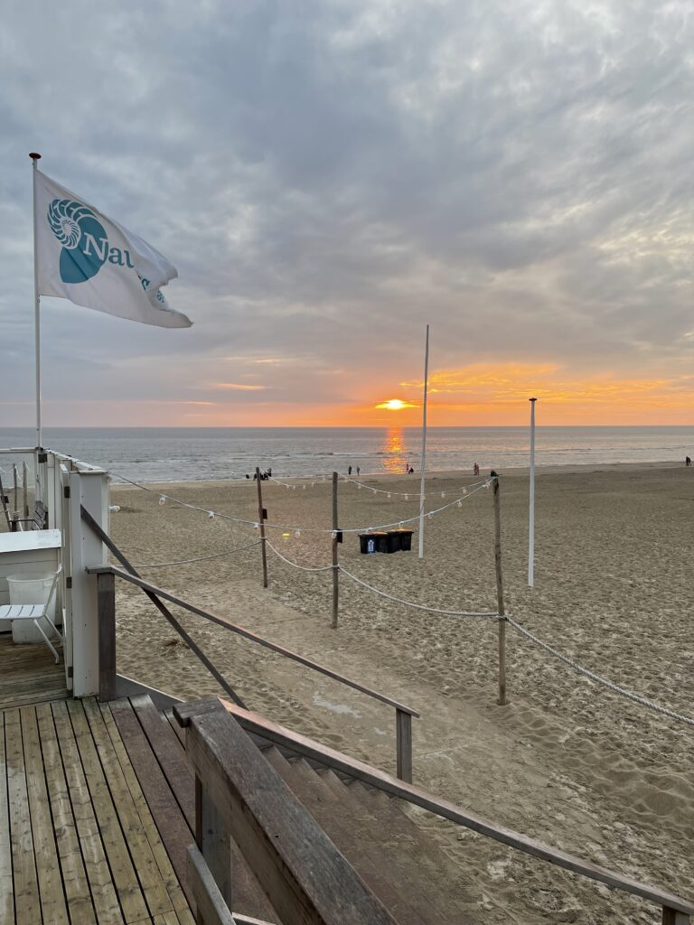 Orange leuchtender Sonnenuntergang bei wolkigem Himmel in Egmond aan Zee am Strand.