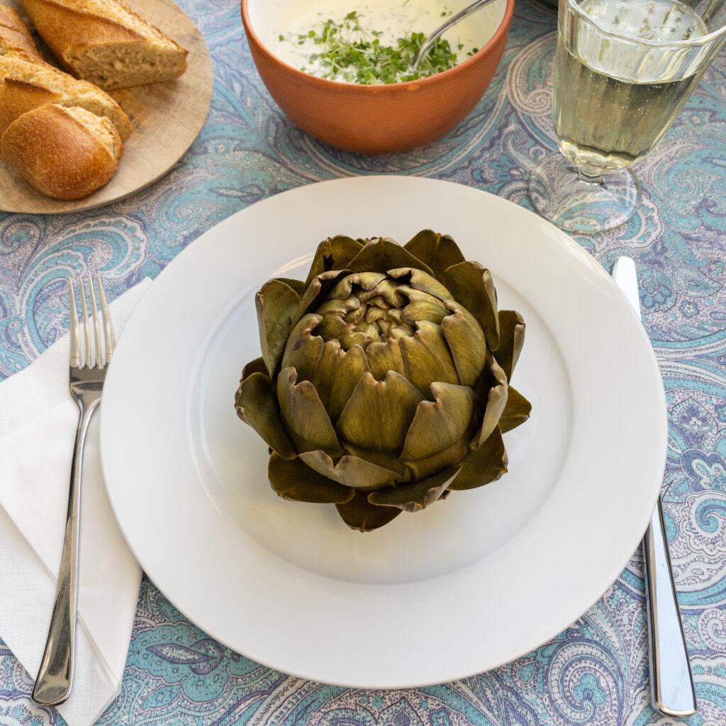 Ein mit einer hellblau-weiß gemusterten Tischdecke gedeckter Tisch. Auf dem weißen Teller liegt eine gekochte Artischocke. Geschnittenes Baguette und ein Joghurt-Kräuter-Dip steht bereit. Dazu ein Glas Weißwein.