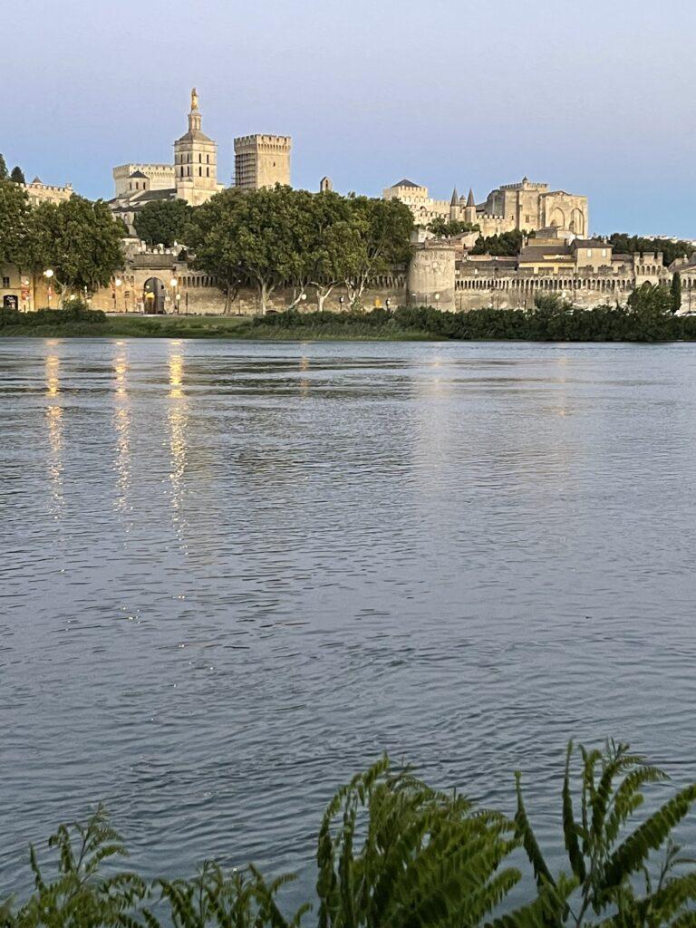 Blick über den Fluss Rhône auf die Stadt Avignon in der Provence. Man sieht die sandfarbene Stadtmauer und den herausragenden Papstpalast, eingerahmt von grünen Bäumen.